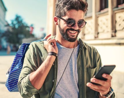 man walking outside wearing sunglasses and holding shopping bag and phone